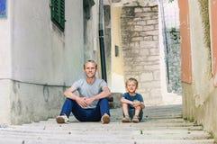 Padre e piccola ubicazione del figlio sulla via croata vecchia della città Immagine Stock