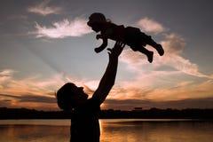 Padre e piccole siluette della figlia al tramonto Immagine Stock