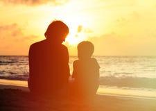 Padre e piccolo figlio che esaminano tramonto sulla spiaggia Fotografia Stock