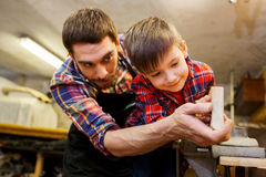 Padre e piccolo figlio con la plancia di legno all'officina Immagini Stock Libere da Diritti