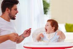 Padre e piccolo figlio del bambino divertendosi durante il tempo di cena Immagini Stock