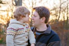 Padre e piccolo figlio in parco o in foresta, all'aperto Immagini Stock Libere da Diritti