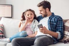 Padre e poca figlia a casa che si siedono ragazza che parla sullo smartphone fotografia stock libera da diritti