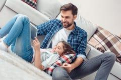 Padre e poca figlia a casa sulla ragazza del pavimento che si trova sulle gambe del padre che giocano gioco sulla compressa digit fotografia stock