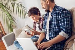 Padre e poco figlio a casa che si siedono sul papà del sofà che lavora al computer portatile che esamina il video di sorveglianza immagine stock libera da diritti
