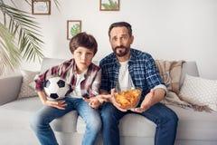 Padre e poco figlio a casa che si siedono sulla ciotola della tenuta del sofà di calcio di sorveglianza della palla e del chip ch fotografia stock