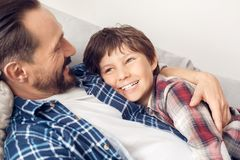 Padre e poco figlio a casa che si trovano sul papà del sofà che abbraccia ragazzo che sorride guardando da parte primo piano drea fotografie stock libere da diritti