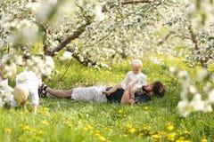 Padre e tre bambini piccoli che si rilassano nel frutteto sulla primavera Da Immagini Stock