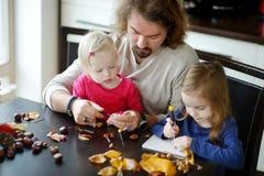 Padre ed i suoi bambini che fanno le creature delle castagne immagine stock libera da diritti