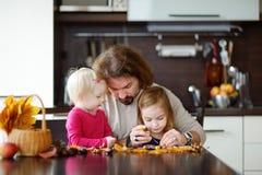 Padre ed i suoi bambini che fanno le creature delle castagne fotografia stock libera da diritti