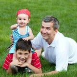 Padre ed i suoi figli nella sosta Immagine Stock