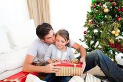 Padre ed i suoi regali di Natale di apertura della figlia Fotografie Stock