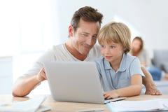 Padre ed il suo piccolo figlio che per mezzo del computer portatile Immagini Stock
