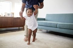 Padre Encouraging Baby Daughter per intraprendere i primi punti a casa immagine stock libera da diritti