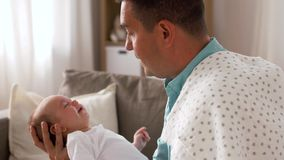 Padre envejecido medio con el bebé gritador en casa almacen de video