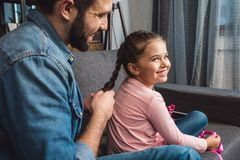 padre felice che fa la treccia dei capelli per la figlia mentre sedendosi sullo strato fotografie stock libere da diritti