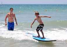 Padre felice che insegna al suo giovane figlio a praticare il surfing