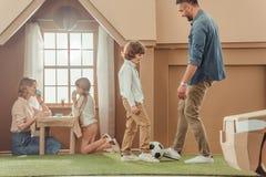 padre felice che insegna al suo som per giocar a calcioe sull'iarda di fotografia stock