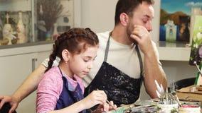 Padre felice che prende le foto della sua piccola figlia sveglia mentre sta disegnando stock footage