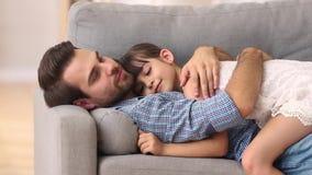 Padre felice che si trova sul sofà che abbraccia insieme l'abbraccio di resto del bambino video d archivio