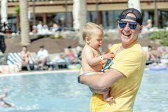Padre felice che spende tempo con suo figlio del bambino dallo stagno nella località di soggiorno immagine stock