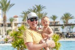 Padre felice che tiene figlio allegro durante la vacanza tropicale immagine stock libera da diritti