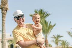 Padre felice che tiene figlio allegro durante la vacanza tropicale fotografia stock