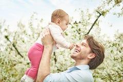 Padre felice che tiene il suo che porta il suo bambino caro fotografia stock libera da diritti