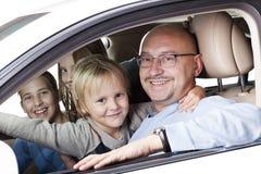 Padre felice con i bambini nell'automobile Immagini Stock
