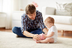 Padre felice con il bambino ed il porcellino salvadanaio a casa Fotografie Stock Libere da Diritti