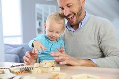 Padre felice con il suo bambino che gioca con i blocchi Immagine Stock