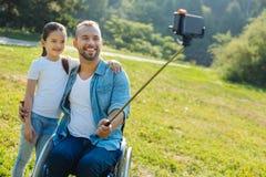 Padre felice con le inabilità che prendono un selfie con la figlia Immagini Stock Libere da Diritti