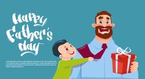 Padre felice Day Family Holiday, papà d'abbraccio del figlio che tiene la cartolina d'auguri attuale della scatola Fotografie Stock Libere da Diritti