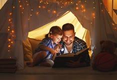 Padre felice della famiglia e figlia del bambino che legge un libro in tenda Immagini Stock