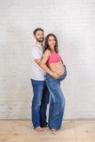 Padre felice della famiglia e madre incinta e vicino ad un muro di mattoni in bianco nella stanza fotografie stock libere da diritti