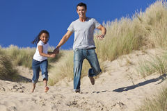 Padre felice e figlia che funzionano alla spiaggia Fotografie Stock Libere da Diritti