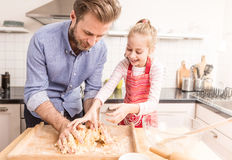 Padre felice e figlia che preparano la pasta del biscotto nella cucina Fotografia Stock