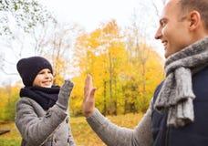 Padre felice e figlio che fanno livello cinque in parco Immagine Stock Libera da Diritti