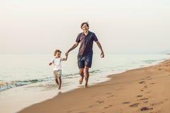 Padre felice e figlio che hanno tempo della famiglia di qualità sulla spiaggia sopra fotografia stock