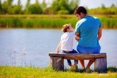 Padre felice e figlio che si siedono sulla sponda del fiume Immagini Stock Libere da Diritti