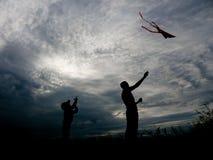 Padre felice e piccolo figlio che lanciano un aquilone al tramonto Fotografia Stock Libera da Diritti