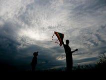 Padre felice e piccolo figlio che lanciano un aquilone al tramonto Fotografia Stock