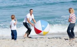 Padre felice e suoi i bambini che giocano con una sfera Fotografia Stock