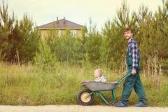 Padre felice in uniforme funzionante che spinge figlio in carriola su una strada rurale vicino alla casa Concetto di giardinaggio Fotografia Stock