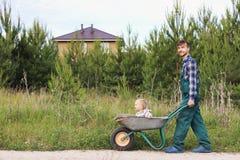 Padre felice in uniforme funzionante che spinge figlio in carriola su una strada rurale vicino alla casa Concetto di giardinaggio Fotografia Stock Libera da Diritti