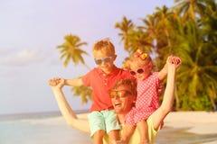 Padre feliz con dos niños en los hombros que se divierten Fotos de archivo libres de regalías