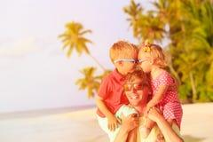 Padre feliz con dos niños en los hombros que se divierten Imagenes de archivo