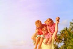 Padre feliz con dos niños en los hombros que se divierten Fotos de archivo