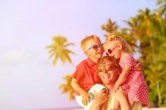 Padre feliz con dos niños en los hombros que se divierten en la playa Imagen de archivo libre de regalías