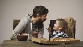 Padre feliz con el hijo del niño que come la pizza Hombre y muchacho que comen el primer del partido de la pizza en casa Amigos q almacen de video